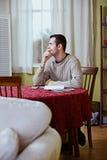 Finanze: L'uomo fa una pausa per pensare mentre fatture di pagamento Fotografia Stock
