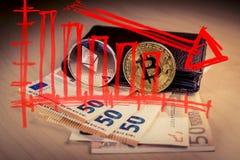 Finanzfallendes Konzept des baissemarktes mit bitcoin und ethereum über einer Geldbörse mit Eurorechnungen lizenzfreie stockbilder