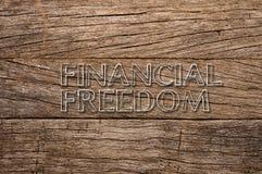 Finanzfreiheit geschrieben auf hölzernen Hintergrund Lizenzfreie Stockfotos