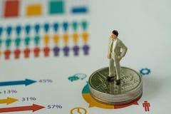 Finanzgeschäftskonzept als Miniaturgeschäftsmann, der an steht Lizenzfreie Stockfotografie