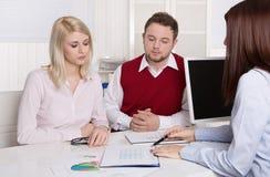 Finanzgeschäftstreffen: junges verheiratetes Paar - Berater und c Stockfotos