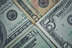 Finanzhintergrund gemacht vom Satz Banknoten im Wert von fünf, zehn, zwanzig und hundert US-Dollars Lizenzfreie Stockfotografie