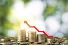 Finanzi e conservi il concetto dei soldi, monete della pila con il growi rosso della freccia Fotografie Stock