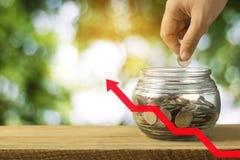 Finanzi e conservi il concetto dei soldi, monete della pila della mano con la freccia rossa Immagine Stock Libera da Diritti