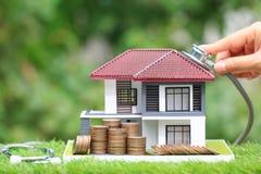 Finanzielle Bedingung, Stapel Münzen Geld und Geschäftsfrau, die Stethoskop verwendet, um Musterhaus auf natürlichem grünem Hinte stockfotografie