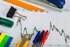 Finanzieren Sie Diagramm auf einem weißen Hintergrund mit Taschenrechner, Münzen, Stiften, Bleistiften und Büroklammern Stockbild