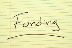 Finanzierung auf einem gelben Kanzleibogenblock Lizenzfreie Stockbilder
