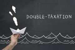Finanzierung, Steuer, Geschäftskonzept Hand, die Segelnpapierschiff mit Text hält: Doppelbesteuerung Lizenzfreies Stockbild