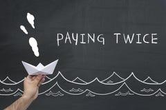 Finanzierung, Steuer, Geschäftskonzept Hand, die Segelnpapierschiff mit Text hält: zweimal zahlen Stockfotografie