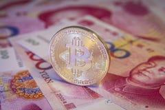 Finanzkonzept mit goldenem Bitcoin über chinesischer Yuanrechnung Lizenzfreies Stockfoto