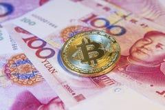 Finanzkonzept mit goldenem Bitcoin über chinesischer Yuanrechnung Stockfotografie