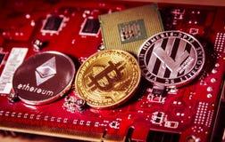 Finanzkonzept mit körperlichem bitcoin, ethereum und Litecoin über einer Videokarte Lizenzfreies Stockfoto