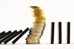 Finanzkrisekonzept mit Stapel des Bargelds unter Domino-Effekt, weißer Hintergrund lizenzfreie stockfotografie