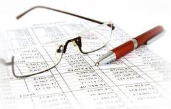 Finanzreport mit Feder und Gläsern Stockfotografie
