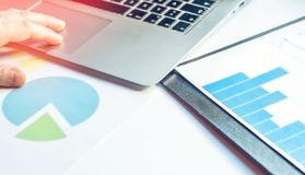 Finanzschreibtischdiagramme und -laptop stockbild