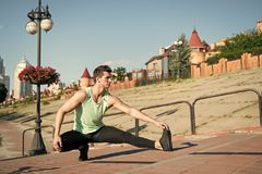 Find balance. Man workout outdoors urban background. You should stretch muscles after workout to achieve best result. Athlete balancing on one leg while royalty free stock photos