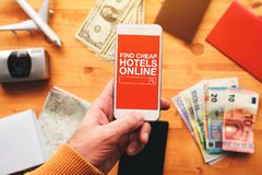 Find cheap hotels online mobile phone app. Overhead view of man holding smartphone and searching affordable accommodation on internet for next vacation trip stock photos