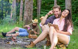Find companion to travel and hike. Friends relaxing near campfire after day hiking or gathering mushrooms. Summer Stock Photo