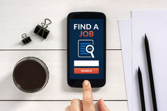 Find a job concept on smart phone screen with office objects Stock Photo