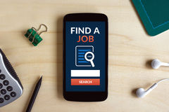 Find a job concept on smart phone screen on wooden desk Royalty Free Stock Photos