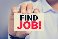 FIND JOB! message on business card shown by a man Stock Photos