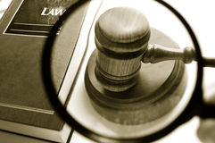 Find law. Magnifying glass examining a judges court gavel, with law book Stock Image