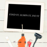 Find it, learn it, do it against tools and tablet on wooden background Stock Photo