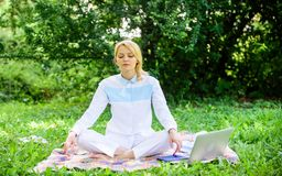 Find minute to relax. Clear your mind. Girl meditate on rug green grass meadow nature background. Every day meditation. Woman relaxing practicing meditation royalty free stock photography