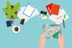 Find a place on a map in a tablet. Top view of the work table with lying holiday planning.  The hands are holding the tablet with a map of a abstract city Royalty Free Stock Photos