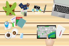 Find a place on a map on a tablet. Top view of the work table of wooden desk on which the holiday planning needs are distributed. The hand  is pointing to the Stock Image