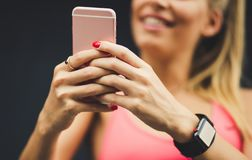Find some exercises on the Internet too. Happy blonde young woman using her smart phone. Focus on hands. Close up image stock image