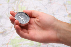 Find way with compass. Hand holding compass and blur map on background Royalty Free Stock Images