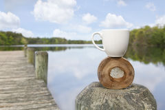 Find your balance. White cup balancing on wooden circle on dock at lake Stock Image