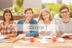Find your college. Group of happy young people working together and looking at camera while sitting at the wooden desk outdoors Stock Photography