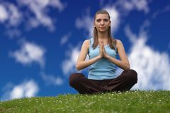 Find your focus. A beautiful young woman sits on a green meadow and does some yoga exercises Royalty Free Stock Photos