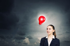 Find your inspiration. Concept of creativity with woman and light bulb hanging from above Stock Images