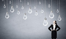 Find your inspiration. Concept of creativity with woman and light bulbs hanging from above Royalty Free Stock Image