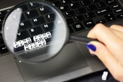 Find your niche under magnifying glass, close up of conceptual text on computer keyboard Royalty Free Stock Photo