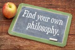 Find your own philosophy on blackboard. Find your own philosophy - motivational words on a slate blackboard against red barn wood Royalty Free Stock Images