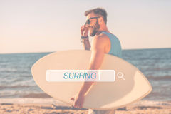 Find your place for surfing. Handsome young man holding skimboard and adjusting eyewear while walking along the beach Stock Image