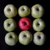 Finden Sie den Eindringling Grüne und purpurrote Äpfel, schwarzer Hintergrund stockbilder