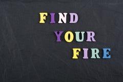 FINDEN Sie IHR FEUER-Wort auf dem schwarzen Bretthintergrund, der von den hölzernen Buchstaben des bunten ABC-Alphabetblockes ver Stockfoto
