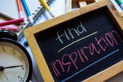 Finden Sie Inspiration auf buntem handgeschriebenem der Phrase auf Tafel, Wecker mit Motivation und Bildungskonzepten stockbild