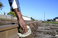 Finders keepers. Dollar bills being picked up from the side of a railway track Stock Photography
