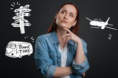 Thoughtful woman touching her chin while dreaming about adventures. Finding adventures. Interested young enthusiastic woman standing alone with her fingers Royalty Free Stock Photos