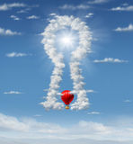 Finding The Answer. With a group of clouds in the sky in the shape of a key hole as a business concept with a red hot air balloon flying up towards the glowing Stock Photography
