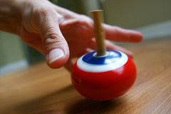Finding the balance. Closeup of a hand, waiting, protecting, reaching for a spinning top Stock Photography