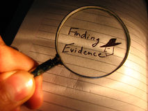 Finding Evidence. A macro image of detective looking for evidence through a magnifying glass stock photo