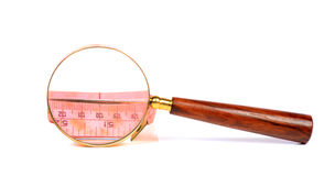 Finding fittness. Beautiful shot of measuring tape with magnifying glass Royalty Free Stock Images
