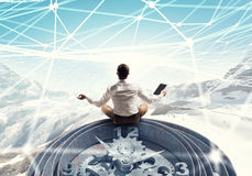 Finding his business center . Mixed media. Young handsome businessman meditating with tablet in hand Royalty Free Stock Photos